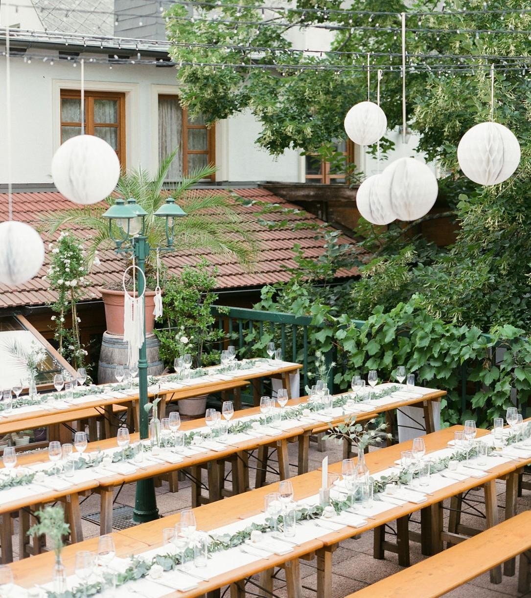 Gedeckte Hochzeitstafel auf Heurigentischen auf einer Terasse