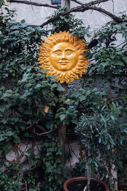 Gelbe Terracotta-Sonne zwischen Efeu
