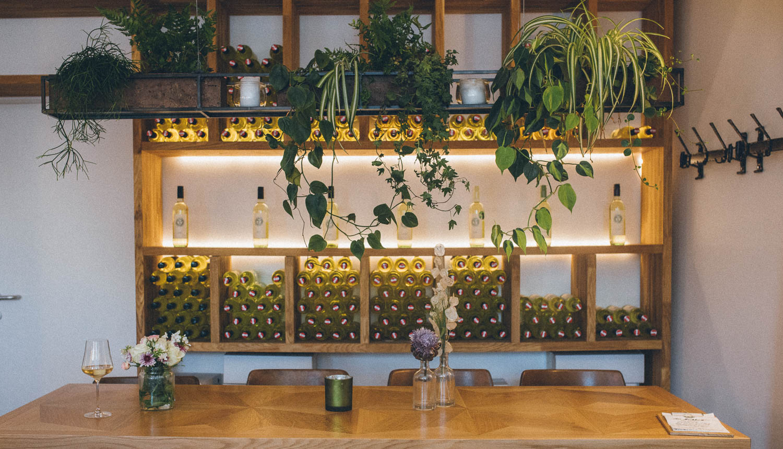 Tisch vor Wandregal mit Weinflaschen